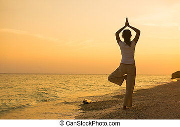 silhouette of a girl performing yoga on beach sunset