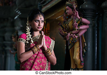 traditional Young indian girl praying in the temple