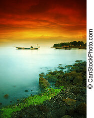 Boat floating under cloudy red sky