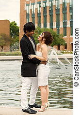 Young Adult Couple Hugging in Front of Water Fountain