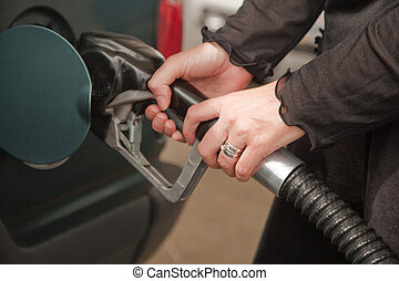 Woman Pumping Gasoline - Womans Hands Pumping Gasoline at...