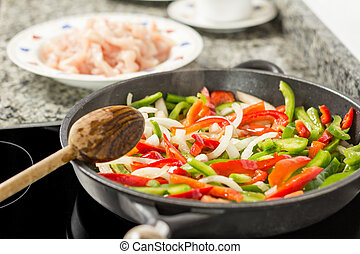 Closeup of female cooking vegetables and chicken in a pan -...