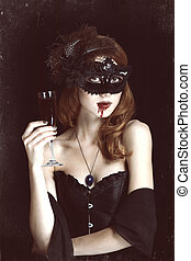 Redhead vampire woman in mask with glass of blood. Photo in...