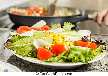 Closeup of fresh salad dish and female cooking in a pan -...
