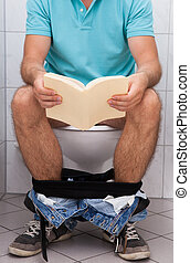 Close-up of a man in toilet reading book indoors