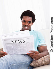 Young African Man Reading Newspaper