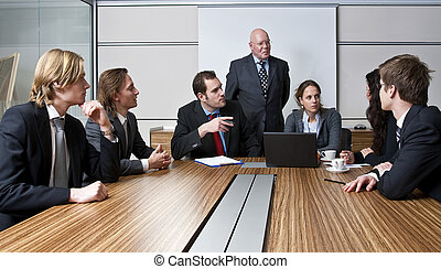 TEAM MEETING - An office meeting between a senior executive...