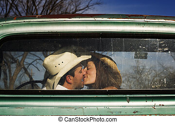 Cowboy Kiss - Cowboy and girlfriend kissing in through the...