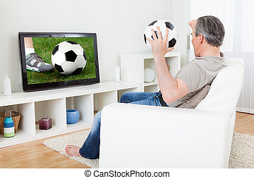 Mature man watching football on television - Portrait of a...