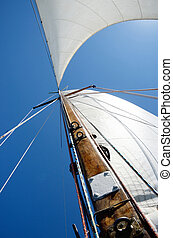 Old wooden mast and white sail, view from deck of boat
