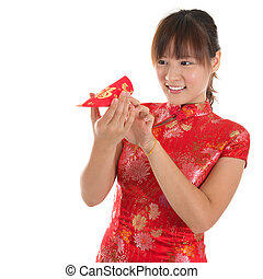 Chinese cheongsam girl peeking into red packets - Asian...