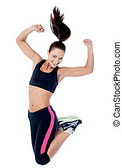 Young girl in sportswear jumping with joy - Girl in sporty...