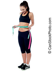 Slim fit woman measuring her waist - Young woman measuring...