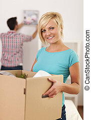 Woman carrying box with items for a new apartment