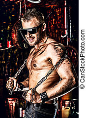hard work - Handsome muscular man with chain in the old...