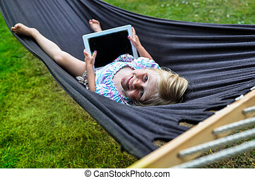 Child hammock tablet - A happy child sitting in a black...