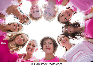 Group of happy women in circle wearing pink for breast...