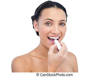 Enthusiastic young natural model applying lip balm on white...