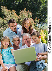 Multi generation family with a laptop sitting in park on a...