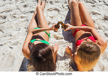 Sexy tanned blonde and brunette having beers