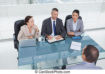 Concentrated business team interviewing experienced man in...