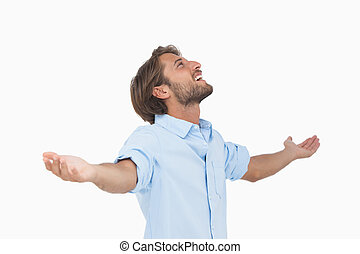 Happy man looking up with arms outstretched