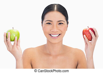 Cheerful black haired model holding apples in both hands on...