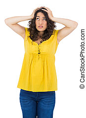 Anxious casual young woman posing on white background