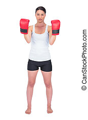 Angry healthy model with boxing gloves posing on white...