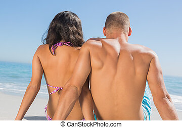 Loving young couple sitting while looking at the sea -...