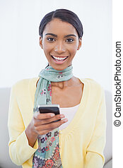 Smiling pretty woman sitting on sofa text messaging -...