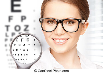 woman with magnifier and eye chart - medicine and vision...