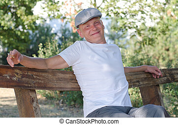 Happy man relaxing outdoors - Happy man with a beaming smile...