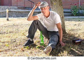 Drunk man sitting at the base of a tree with a bottle of...