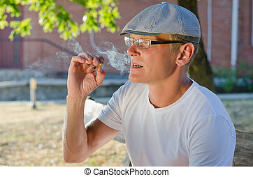 Man smoking a cigarette or joint - Man wearing glasses and a...