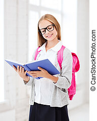 girl reading book at school - education and school concept -...