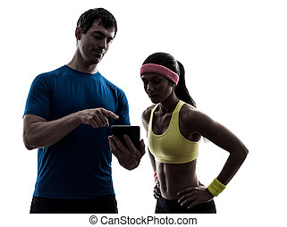 woman exercising fitness man coach using digital tablet -...