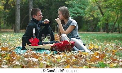 Picnic in in autumn park - Young couple enjoying their...