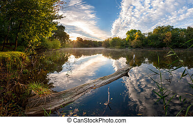 Morning on river with majestic clouds reflection in water