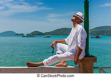 The man at the resort in a white suit and hat sitting on a...