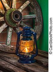 kerosene lamp against the background wagon wheel - kerosene...