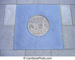 coin of ten cents in pavement - Former Dutch ten cents coin...