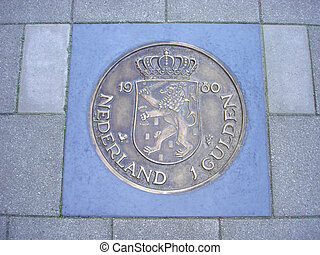 coin of one guilder in pavement - Former Dutch one guilder...