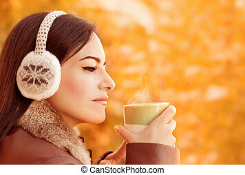 Female have coffee in autumn park