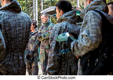 Players in paintball prepare for fight