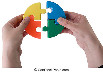 Multi-coloure puzzle - Hands joining slices of a puzzle on a...