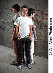 Three guys - Three boy standing close in front of graffiti...