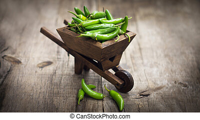 Jalapenos chili pepper in a miniature wheelbarrow - Green...