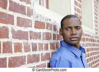 guy against brick wall - half length portrait of one African...