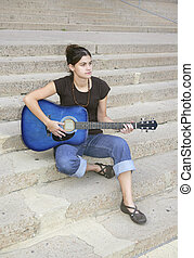 woman guitarist playing - one young brunette woman playing a...
